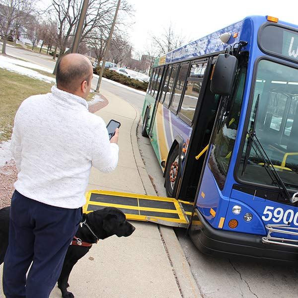 Man holding phone with service dog near bus