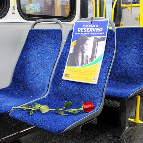 Rosa Parks portrait on empty seat with rose